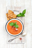 Cold gazpacho soup with ice and basil over white background Royalty Free Stock Photo
