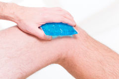 Cold gel compress on the knee. Man using cold gel compress on knee to reduce pain stock photography