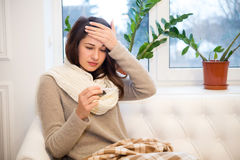 A cold girl checks her temperature Royalty Free Stock Image
