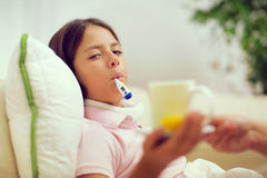 Cold girl lying on the couch with a thermometer Royalty Free Stock Photos