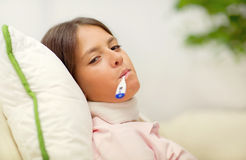 Cold girl lying on the couch with a thermometer Stock Photo