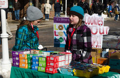 Cold girl scouts and cookies. Two cold girl scouts shiver in the winter cold, as they sell girl scout cookies outdoors at a winter festival in Michigan royalty free stock photo