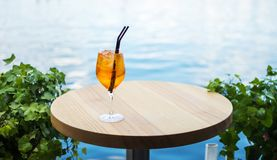 Cold glass of aperol spritz appetizer stand on table near the river royalty free stock photography