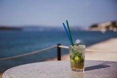 Cold glass of Mojito stand on table near the sea stock photography