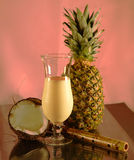 A cold glass of pina colada against a pink background Stock Photos
