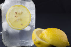 Cold glass of water with ice cubes and a slice of lemon. Royalty Free Stock Photos