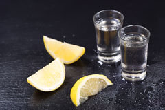Cold glasses of vodka with slices of lemon Stock Image