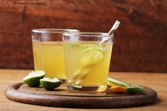 Cold gold soft drink from lime and honey with gold straw Stock Image