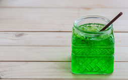 Cold green soda. In a big glass over wooden background Stock Image