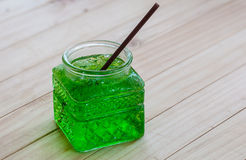 Cold green soda. In a big glass over wooden background stock photos