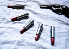 Cold gun with lipsticks. On a bed Royalty Free Stock Image