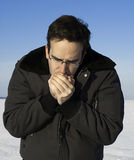 Cold Hands. A man outside in the winter is warming his hands by breathing on them Stock Images