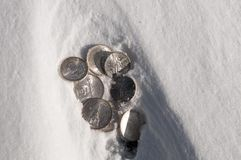 Cold hard cash - silver coins in snow Royalty Free Stock Image