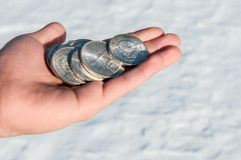 Cold hard cash - silver coins in a young man's hand Stock Photo