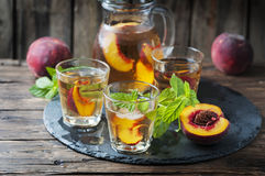 Cold healthy tea with peaches and mint Royalty Free Stock Photography