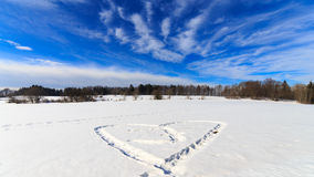 Cold Heart. Heart in the snow under blue sky Royalty Free Stock Images
