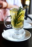 Yellow herbal tea with lemon and rosemary in a glass cup on a white plate Stock Photos