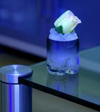 Cold ice drink with white rose. Cold blue composition, glass with ice and rose Royalty Free Stock Image