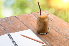 Cold iced coffee in jar cup on table with notebook relax time. Royalty Free Stock Images