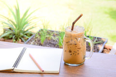 Cold iced coffee in jar cup on table with sketchbook Stock Photos