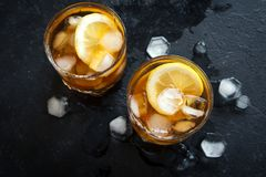 Iced tea. Cold iced tea with lemon and ice cubes over black stone background, copy space, top view. Iced summer drink royalty free stock photography