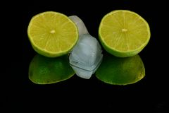 Refreshing, two halfs of green lime and two ice cubes. Cold, juicy, green limes with some ice! Wonderful, rich green color royalty free stock photos