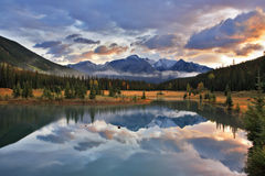 The cold lake, forest and snow mountains in Canada. Dark blue cold lake, forest coast and snow mountains in Canada Royalty Free Stock Photography