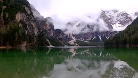 Cold lake Pragser Wildsee and misty mountains in the Alps, Italy stock video footage