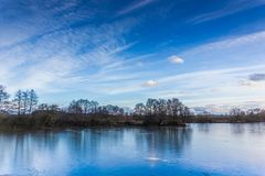 Cold lake under a blue sky in the winter. Stock Photography