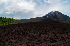 Cold lava residual in front of not active volcano Royalty Free Stock Photos