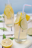 Cold lemon drink with slices of lime and lemon Stock Image