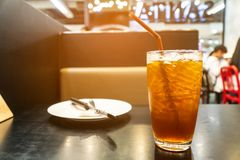 Cold lemon tea on the table. With plates and spoons. stock image