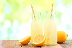 Cold lemonade in bottles with de-focused outdoor background Royalty Free Stock Images