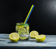Cold lemonade in bottles with lemons. On a black background stock photo