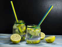Cold lemonade in bottles with lemons. On a black background royalty free stock photography