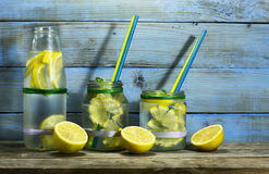 Cold lemonade in bottles with lemons. On a blue wooden background stock image
