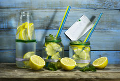Cold lemonade in bottles with lemons. On a blue wooden background stock photo