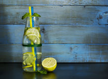 Cold lemonade in bottles with lemons. On a blue wooden background royalty free stock image