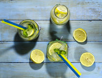 Cold lemonade in bottles with lemons. On a blue wooden background. Top view stock image