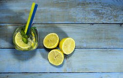 Cold lemonade in bottles with lemons. On a blue wooden background. Top view royalty free stock images