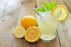 Cold lemonade with lemon slices and mint on rustic wood Stock Images