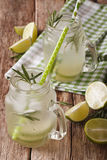 Cold lemonade with lime, ice and rosemary close up in a glass ja Stock Images