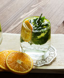 Cold lemonade with orange and mint. Fresh homemade lemonade with orange and mint on the background of an old wooden board. Selective focus Royalty Free Stock Photography