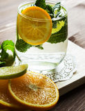 Cold lemonade with orange and mint. Cold lemonade with orange and mint in a glass cup on a wooden stand. Selective focus Stock Photography