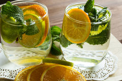 Cold lemonade with orange and mint. Cold homemade lemonade in a glass cup on a wooden stand. Selective focus. Close-up Royalty Free Stock Photos