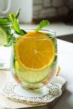 Cold lemonade with orange and mint. Homemade lemonade on the kitchen table. Selective focus Stock Photos