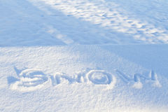 Cold letters of SNOW traced into new snowfall Royalty Free Stock Photo
