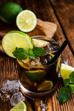 Cold Longdrink (Cuba Libre). With brown rum and fresh lime on rustic wooden background stock image
