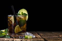 Cold Longdrink (Cuba Libre). With brown rum and fresh lime on rustic wooden background stock images