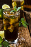Cold Longdrink (Cuba Libre). With brown rum and fresh lime on rustic wooden background royalty free stock images